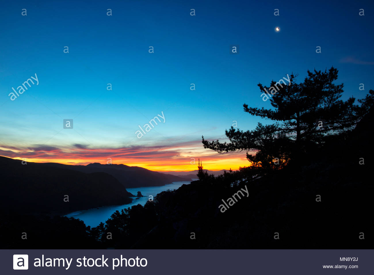 Clouds, turned fiery red by the rising sun, and the crescent moon are in the sky over Muir Beach in the Golden Gate National Recreation Area near San  - Stock Image