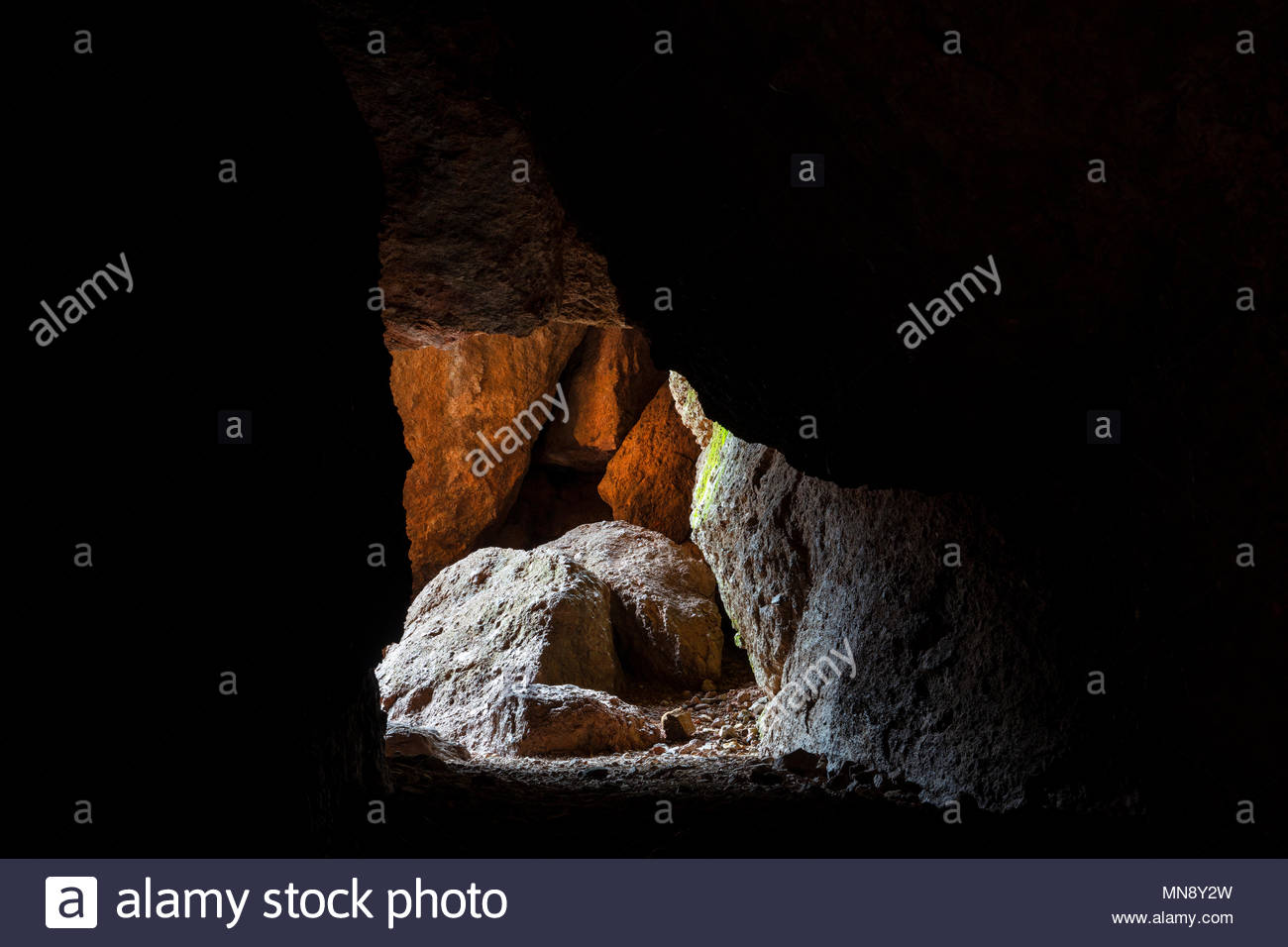 Light shines into a section of the Balconies Cave, a talus cave in Pinnacles National Park, California. The park's high peaks are partial remnants of  - Stock Image