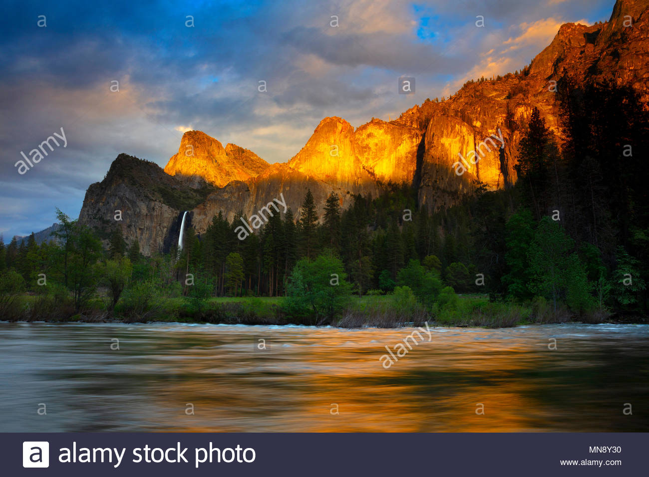 The golden light of sunset reflects off several Yosemite peaks, including the Leaning Tower and Dewey Point, onto the Merced River at Valley View in Y - Stock Image