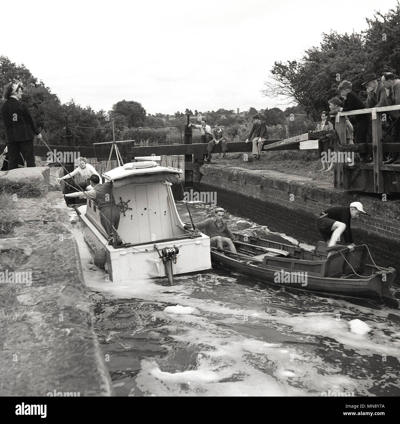 1950s, historical, people look on as a small motorboat and a wooden rowing boat try to manoeuvre pass each other on a rural canal lock, England, UK. - Stock Image