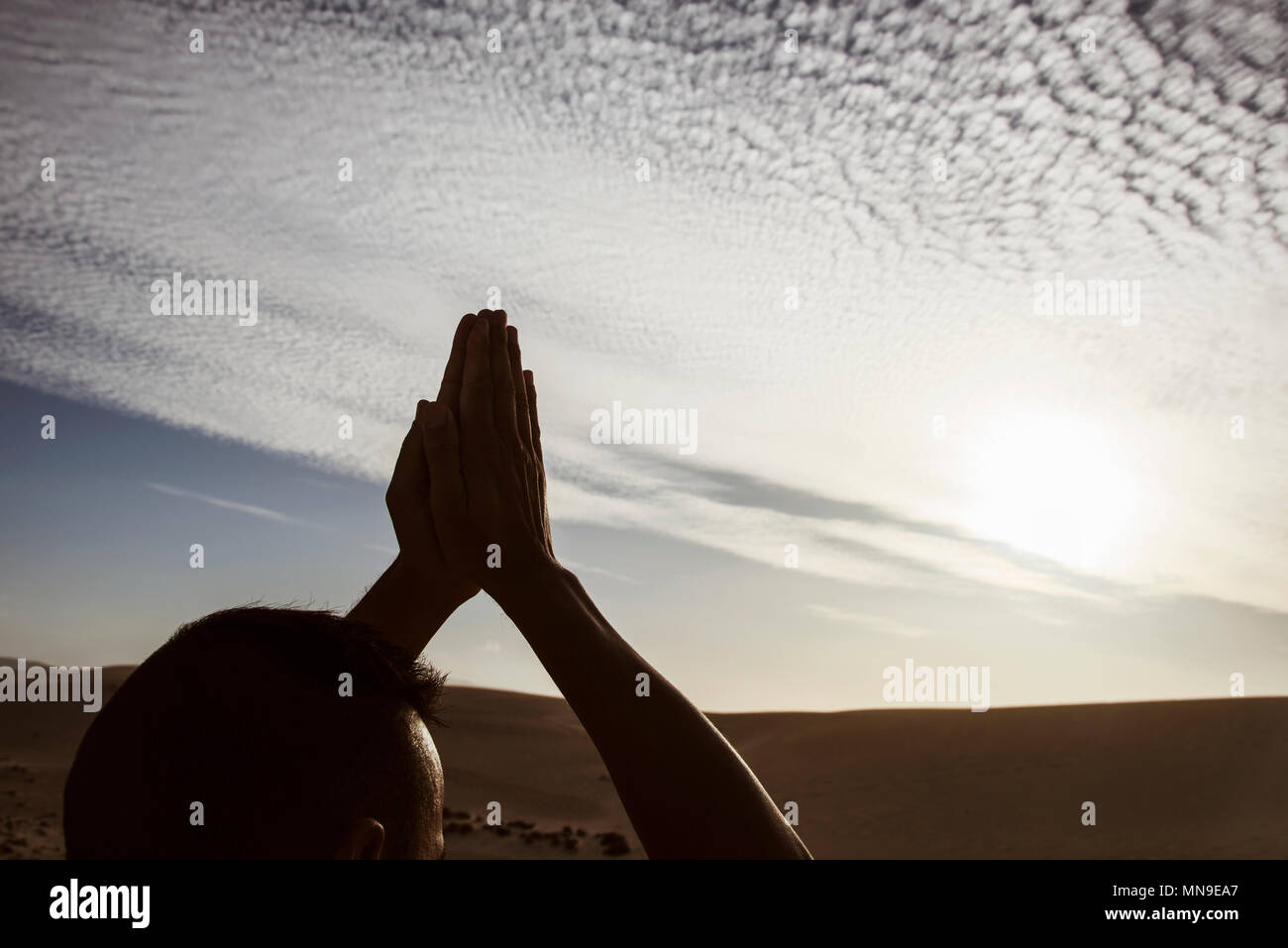closeup of a young caucasian man practicing yoga outdoors, against a cloudy sky, with the sun in the background - Stock Image