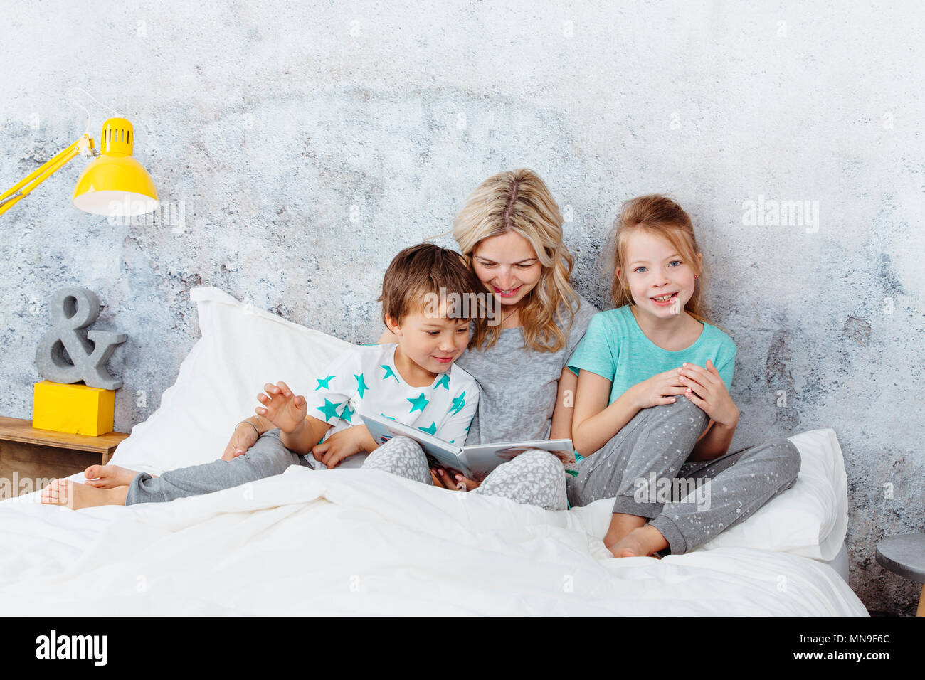 Beautiful mother is reading a story to her children Stock Photo