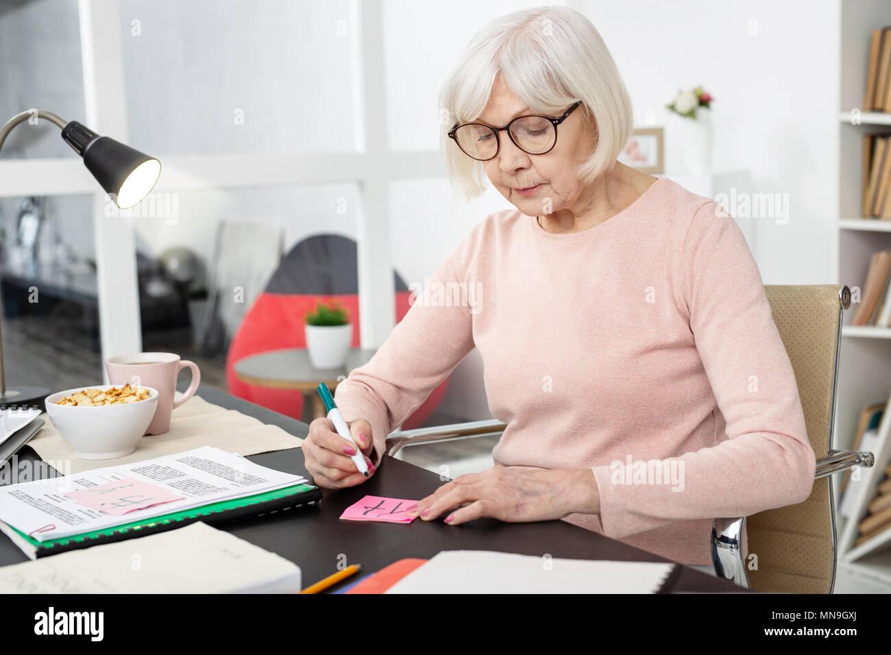 Focused mature woman drawing hieroglyph - Stock Image