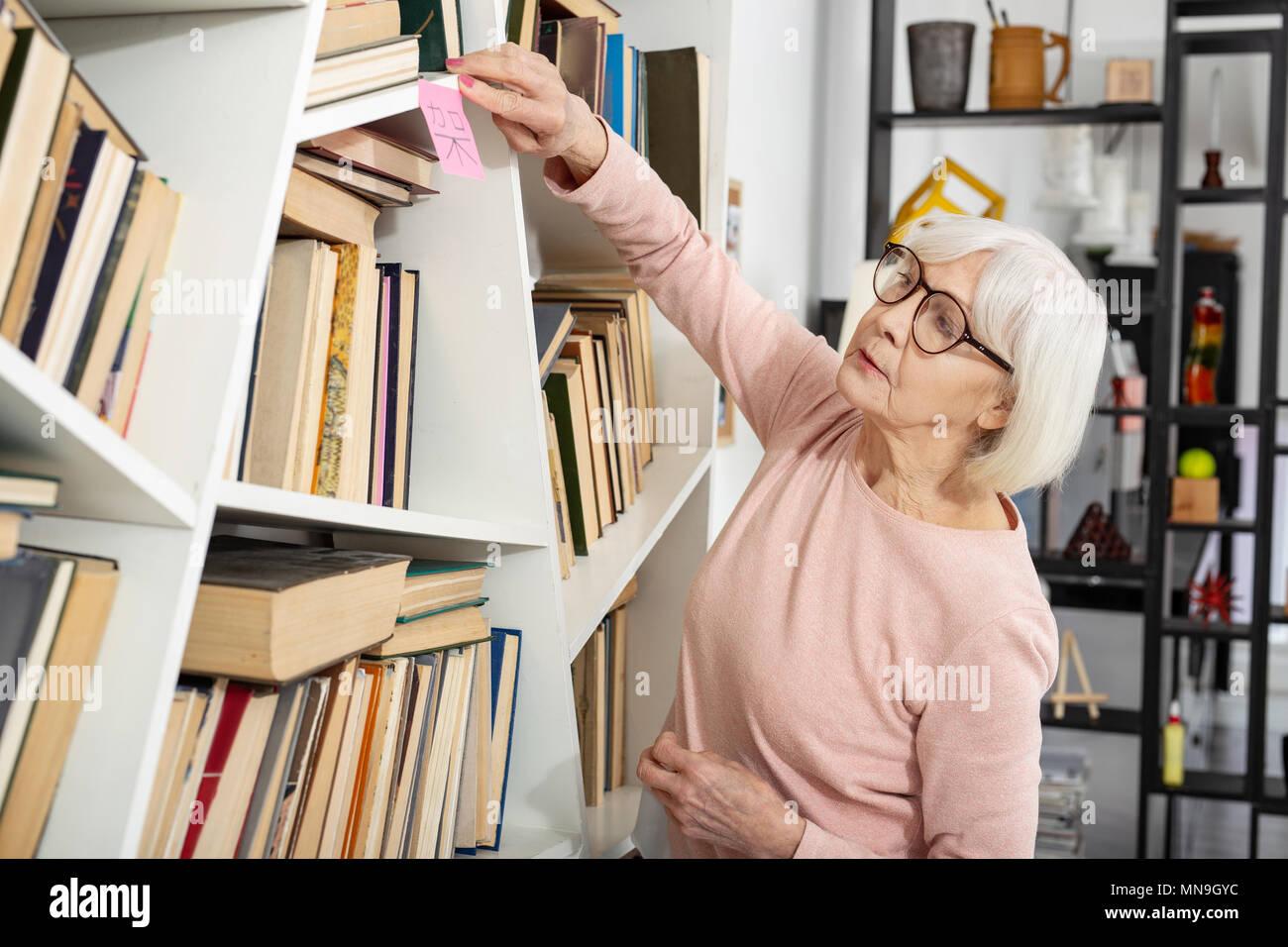 Clever mature woman sticking on shelf hieroglyph - Stock Image