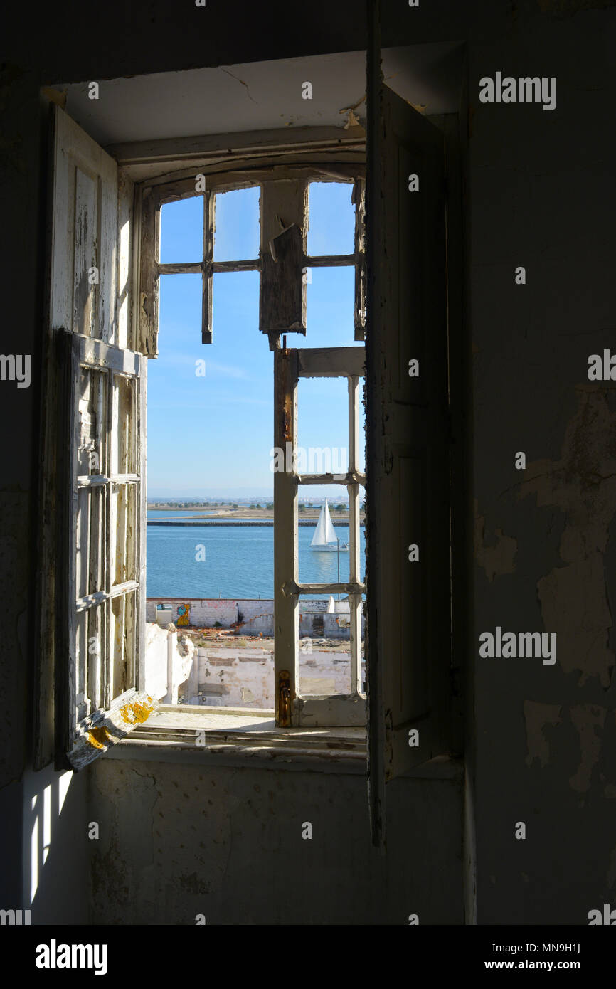 View of a sailing boat from an old, dilapidated window in an abandoned apartment in Portugal Stock Photo