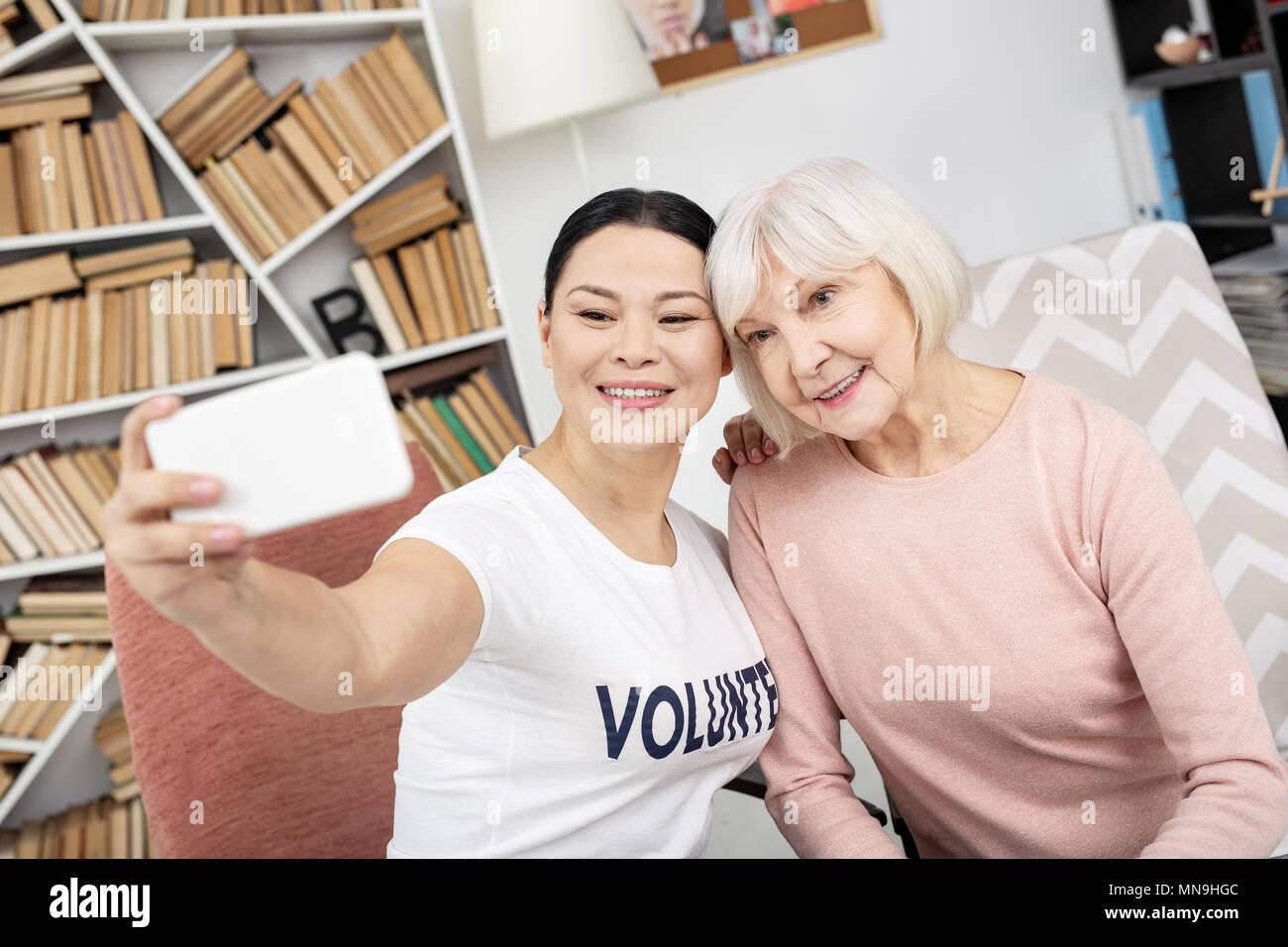 Joyful volunteer and senior woman taking selfie - Stock Image