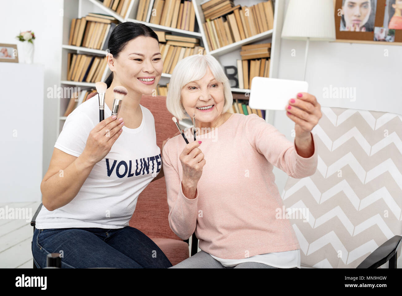 Happy volunteer and senior woman smiling for selfie - Stock Image