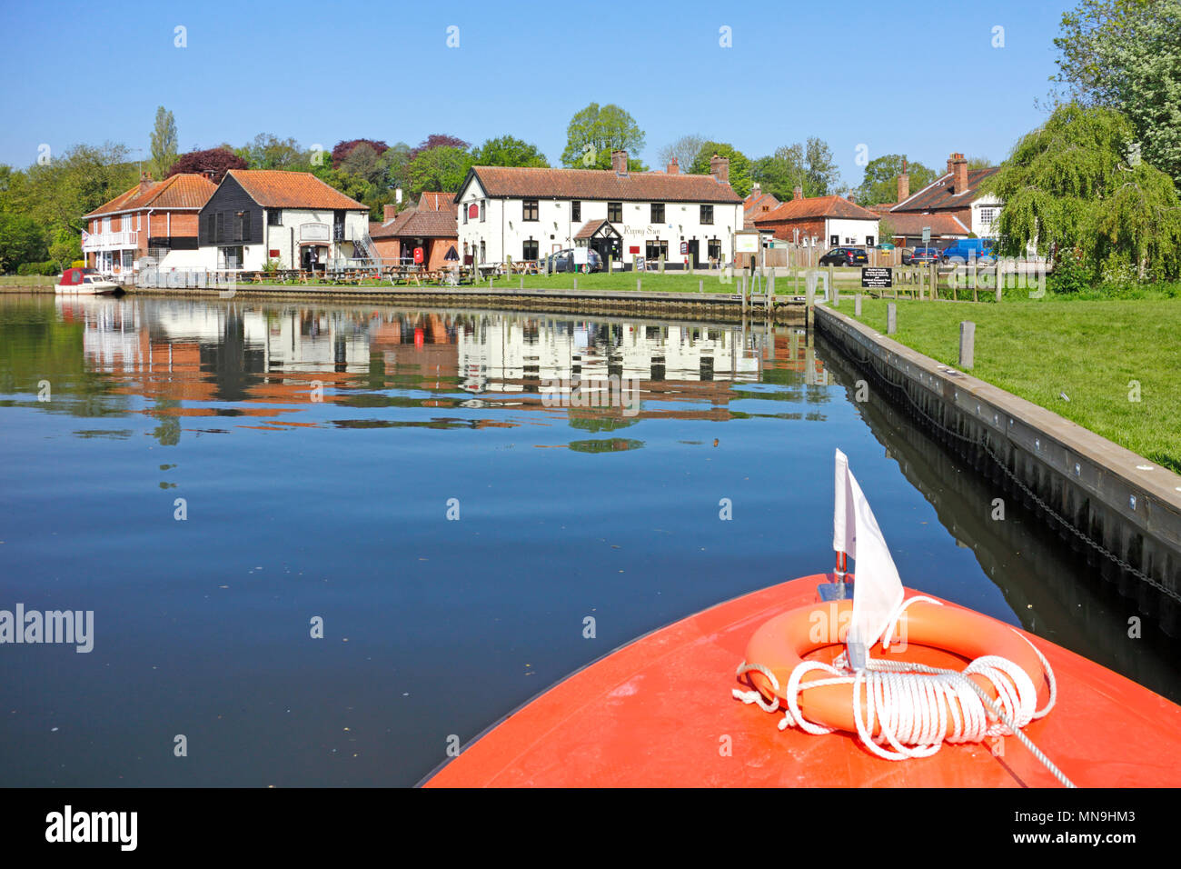 A day hire boat approaching the Rising Sun on the River Bure on the Norfolk Broads at Coltishall, Norfolk, England, United Kingdom, Europe. - Stock Image