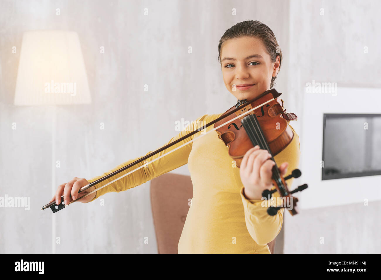 Positive delighted girl preparing for performance - Stock Image