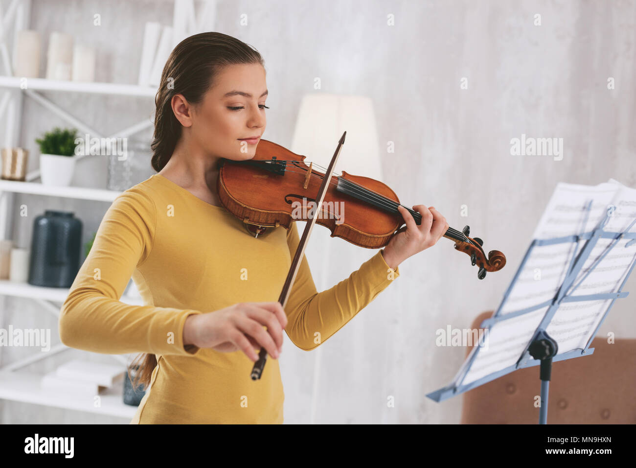 Attentive girl learning classical work - Stock Image