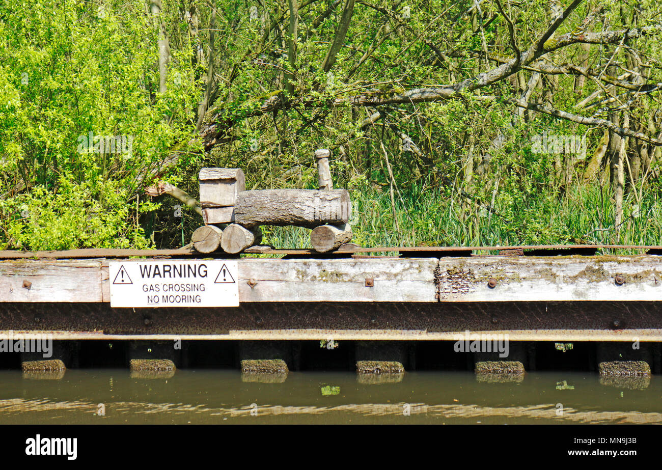 A naïve model wooden train by a gas transmission pipeline crossing on the River Bure near Belaugh, Norfolk, England, United Kingdom, Europe. - Stock Image