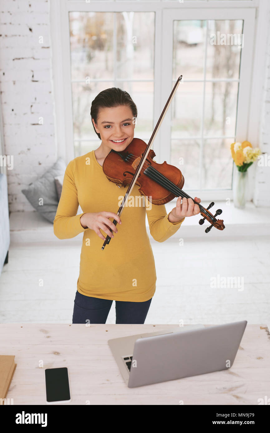 Joyful schoolgirl learning classical melody - Stock Image
