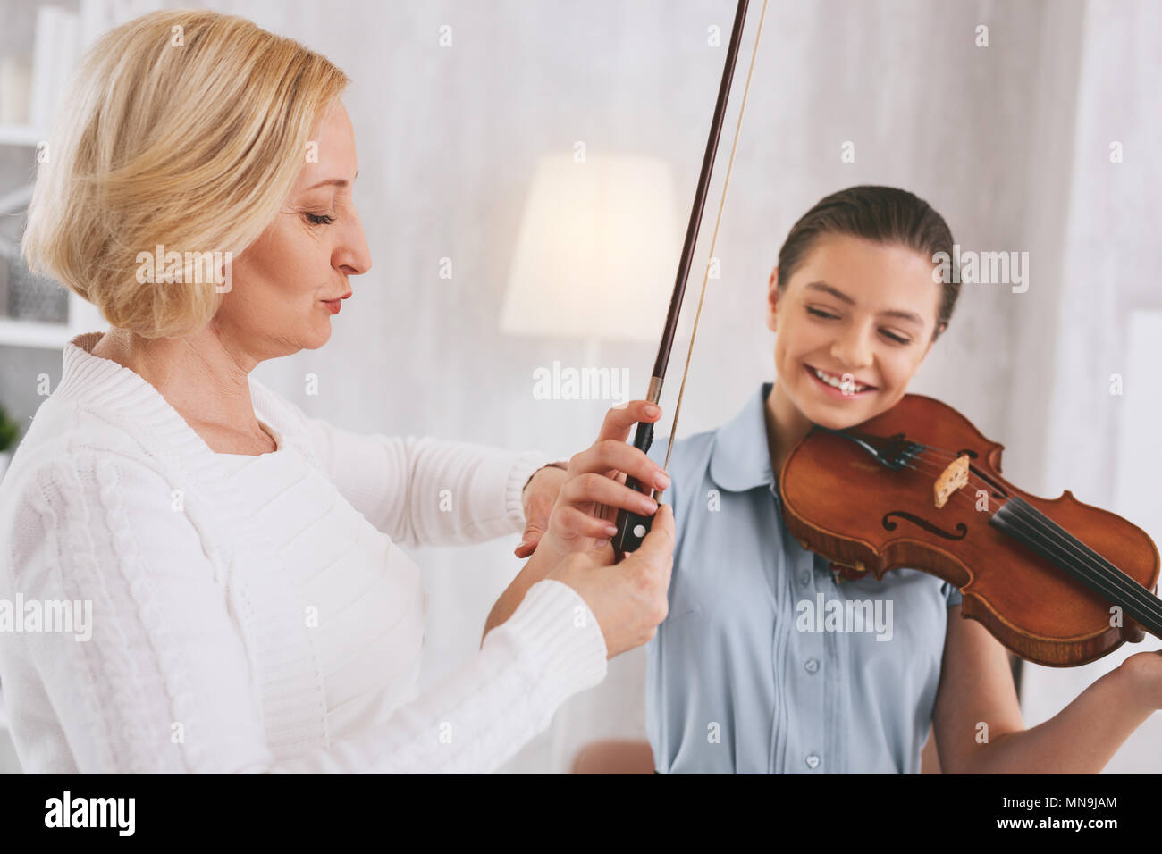 Serious tutor demonstrating the way of playing - Stock Image