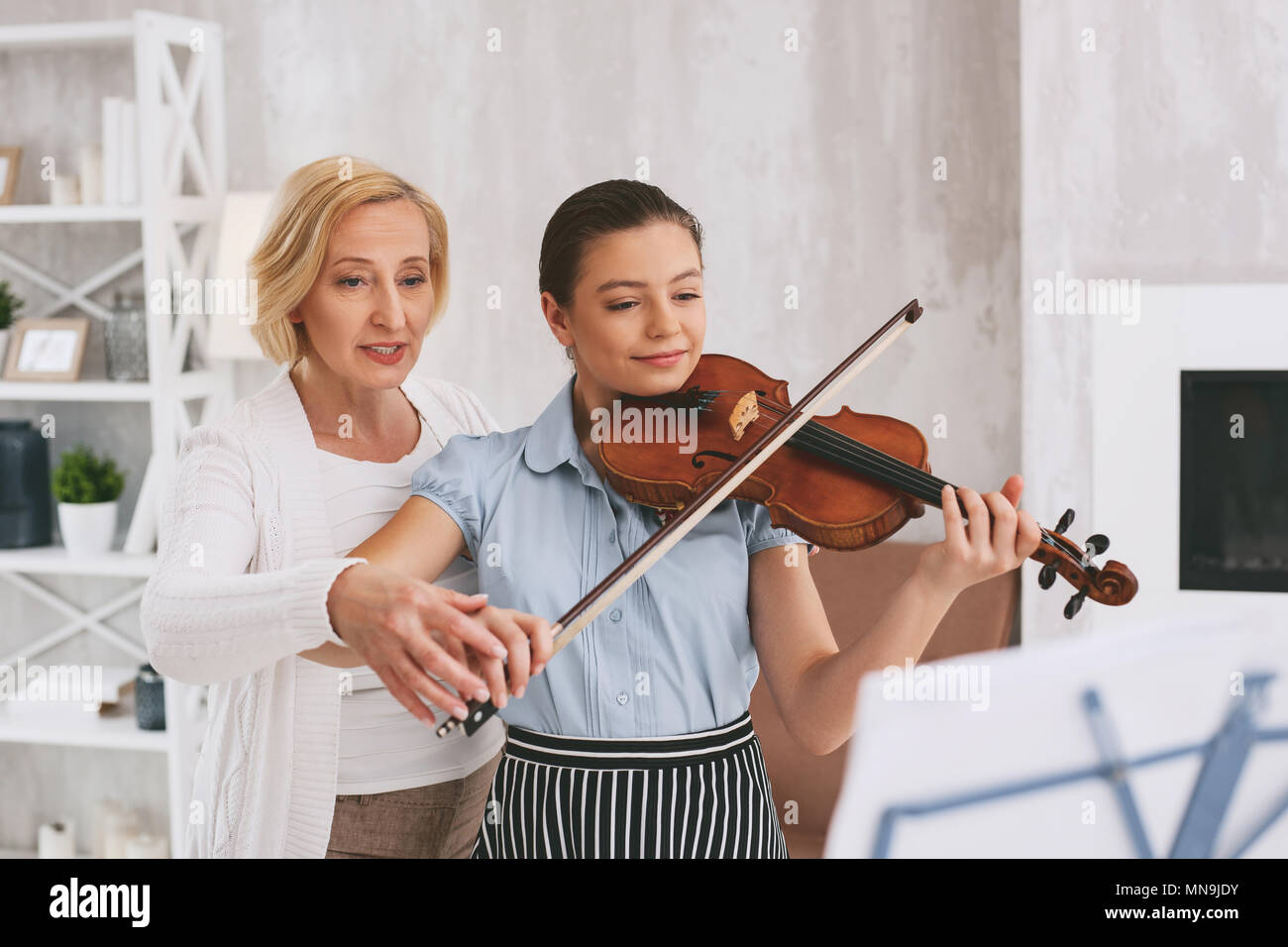 Professional violinist teaching her student - Stock Image