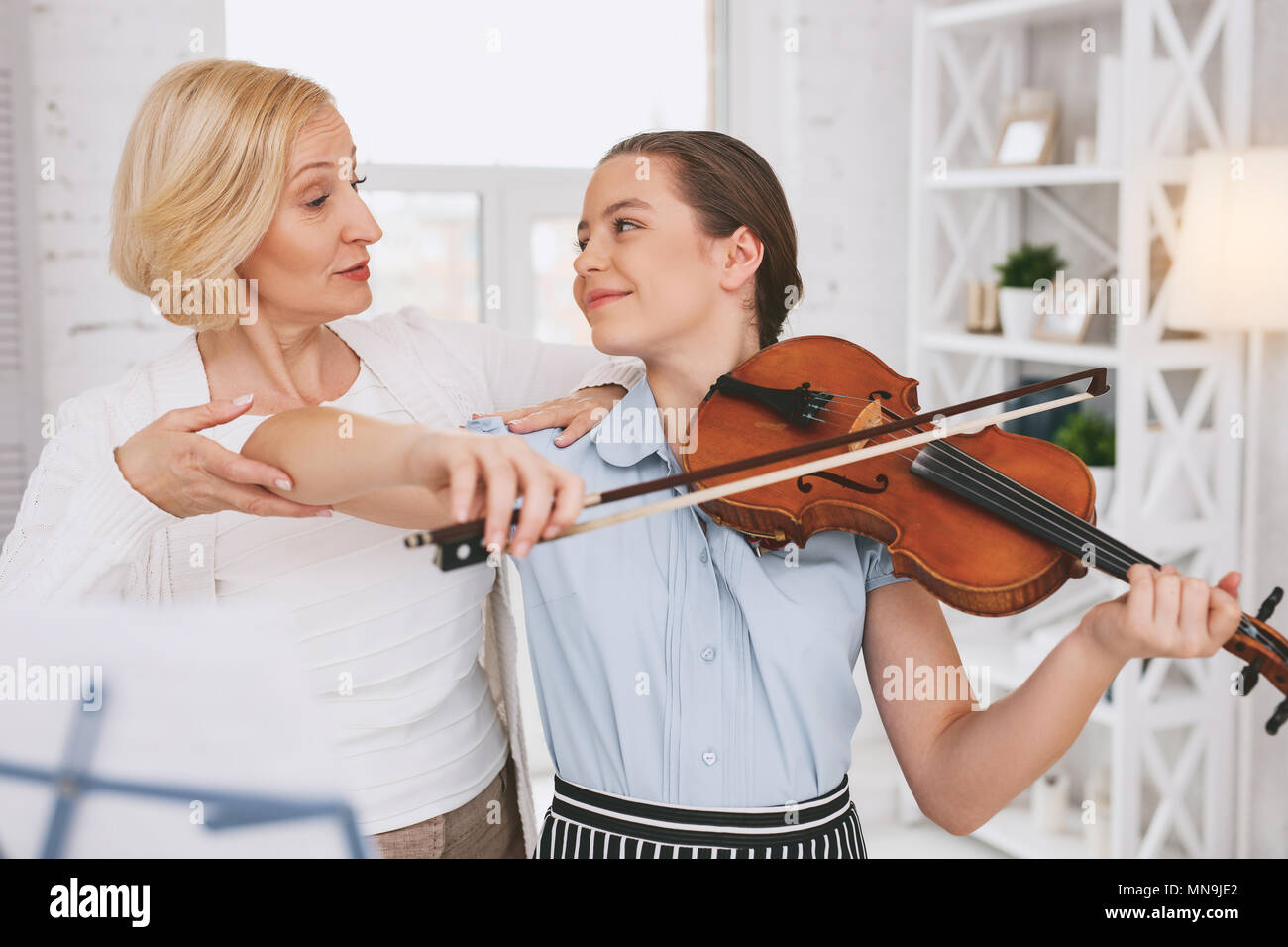 Attentive woman helping her student - Stock Image
