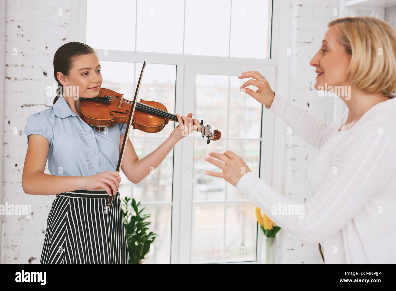 Delighted tutor raising her hands - Stock Image