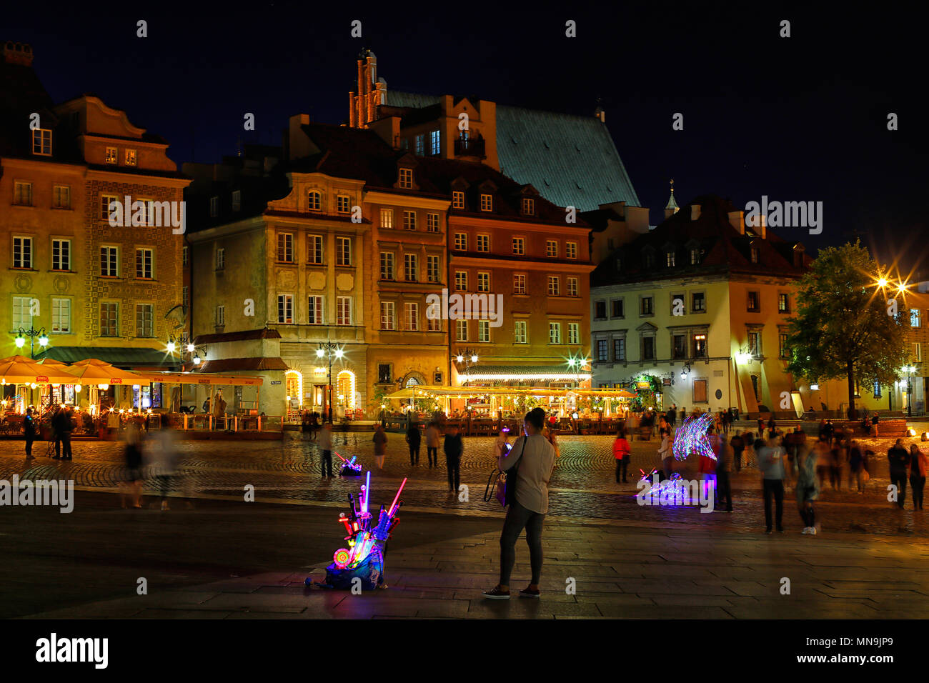 The castle square in Warsaw is visited by tourists at any time of the day. - Stock Image