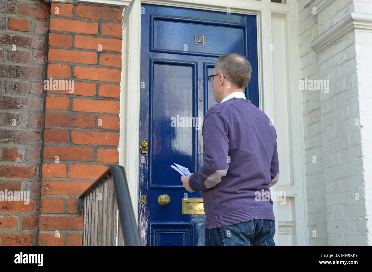 Male canvasser knocking on a blue door and standing outside & Male canvasser knocking on a blue door and standing outside Stock ...