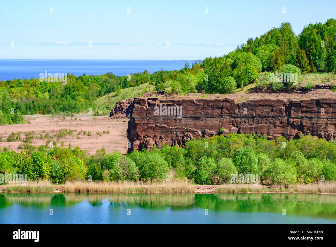 Rock Wall in an old quarry with a lake - Stock Image
