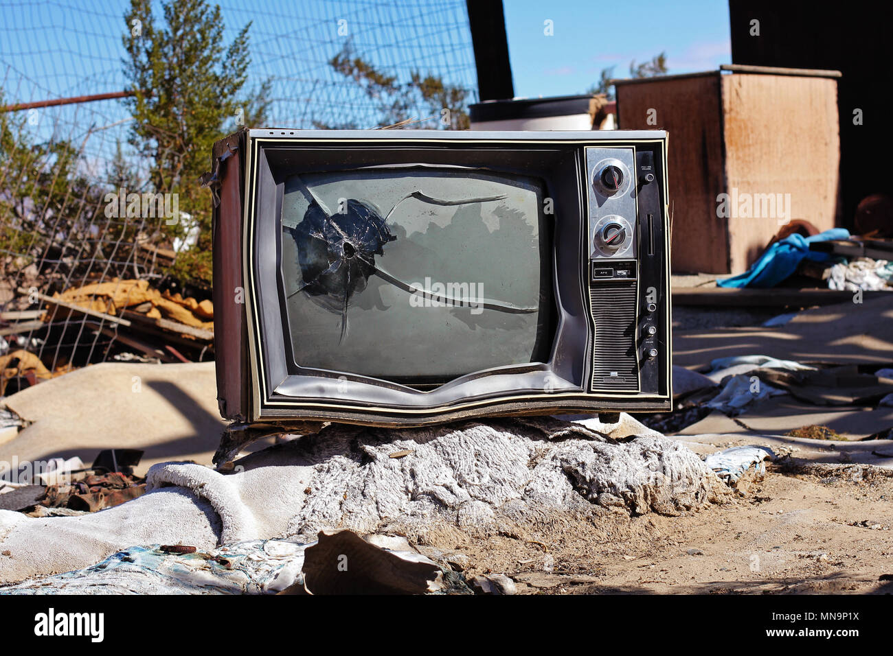 An old TV, shattered by a bullet hole, in a garbage pile behind a wrecked abandoned house, Wonder Valley, California, USA. High desert, Mojave. - Stock Image
