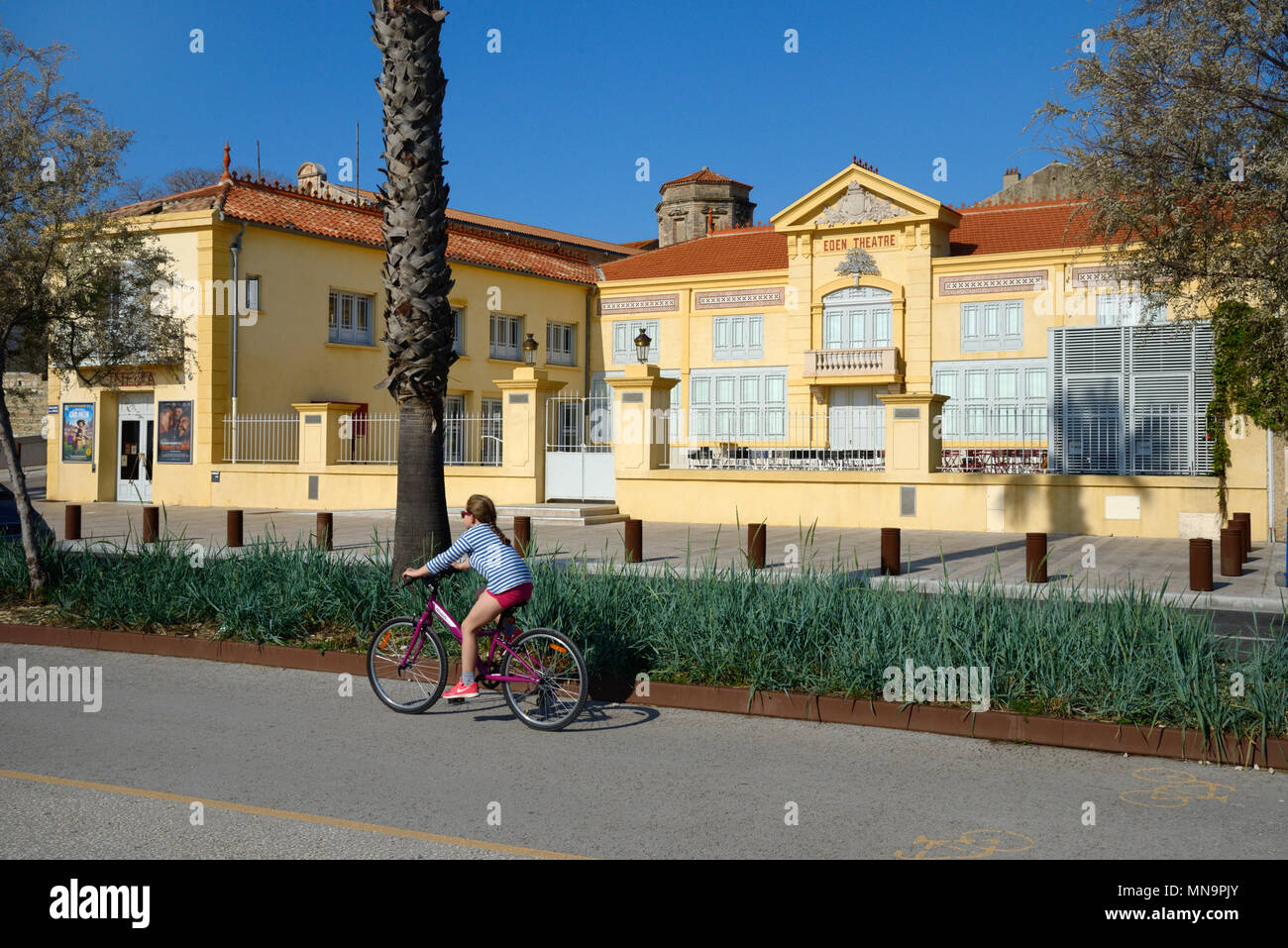 Girl Cycling in Cycle Lane Past the Historic Eden Theatre or Eden Theater, one of the world's earliest cinema or movie theatre, La Ciotat, France - Stock Image
