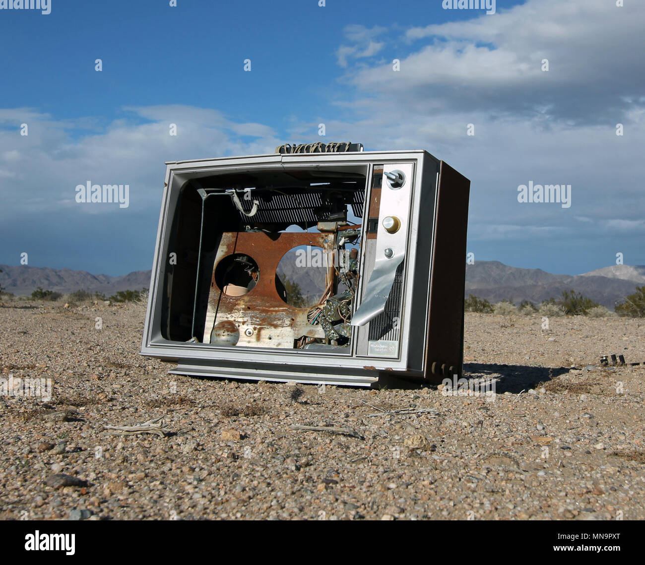 An old TV, a television, broken and no screen, sits on the sand of the high desert, the Mojave, in Wonder Valley, near Joshua Tree, California, USA - Stock Image