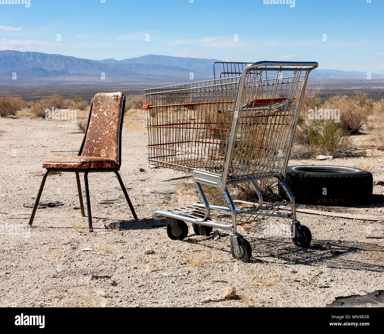 An old chair, shopping trolley, tire, an unlikely still life grouping looks across California's Wonder Valley, in the High Desert, the Mojave, USA. - Stock Image
