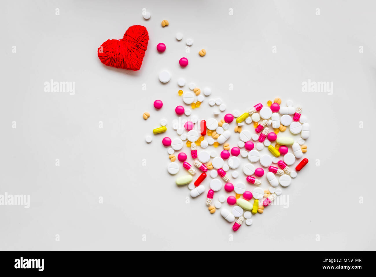 red heart with different pills over white background, healthy life concept.heart disease, heart condition. Problems with health. Arrhythmia, heart failure.impact of tablets on pregnancy.Copy space - Stock Image