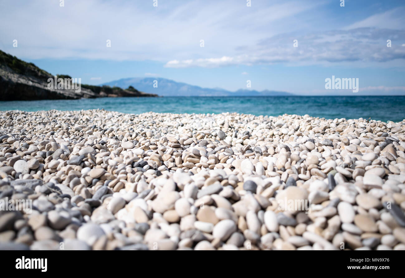 Beach with pebbles and blue sea and sky. - Stock Image