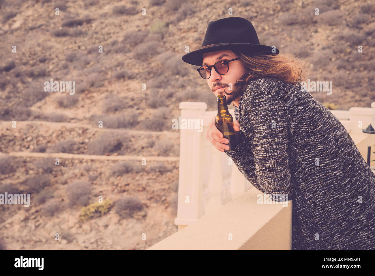 long hair beautiful young man drinking beer outdoor on the rooftop terrace with mountain and nature in background. vingtage retro filter. black hat an - Stock Image