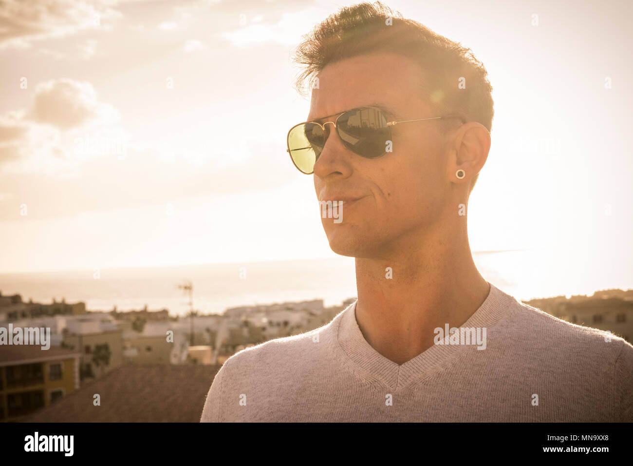 beautiful young man with sunglasses like aviator model looking in front. beautiful golden sunset on the background with ocean and amazing view from hi - Stock Image