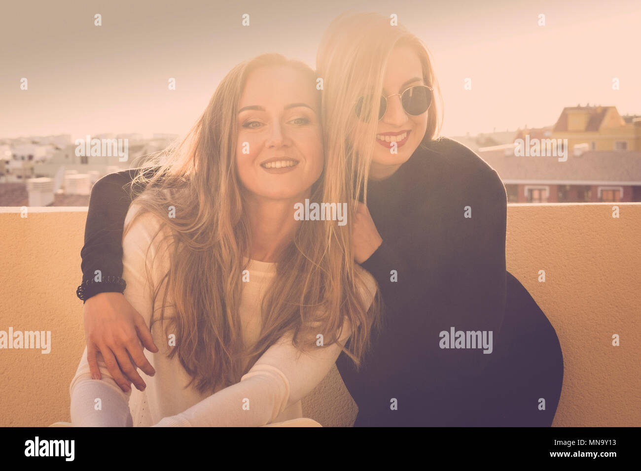 smile and fun for a blonde girls couple outdoor on the terrace roodtop. sunlight in backlight bright image with friendship concept. beautiful models h - Stock Image