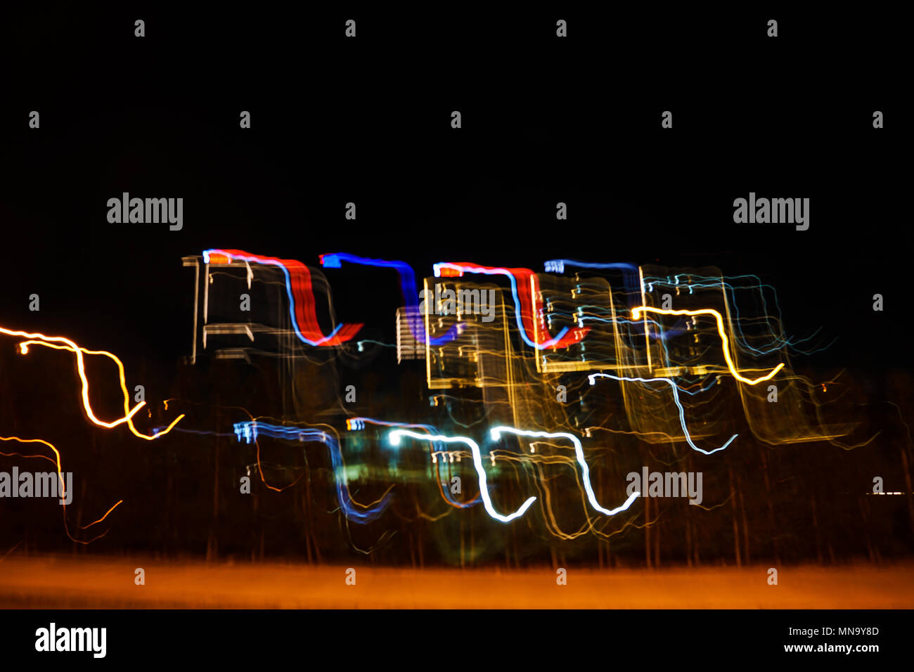 Multi colored abstract light painting at night tme as a background - Stock Image