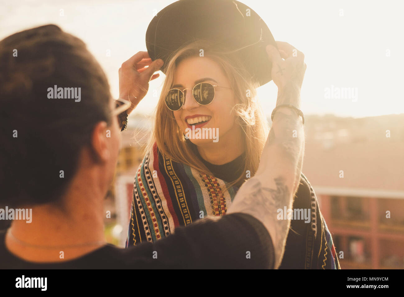 outdoor activity for couple of man and blonde young beautiful woman having fun together. he puts a hat on her head and she smile. sunlight and rooftop - Stock Image