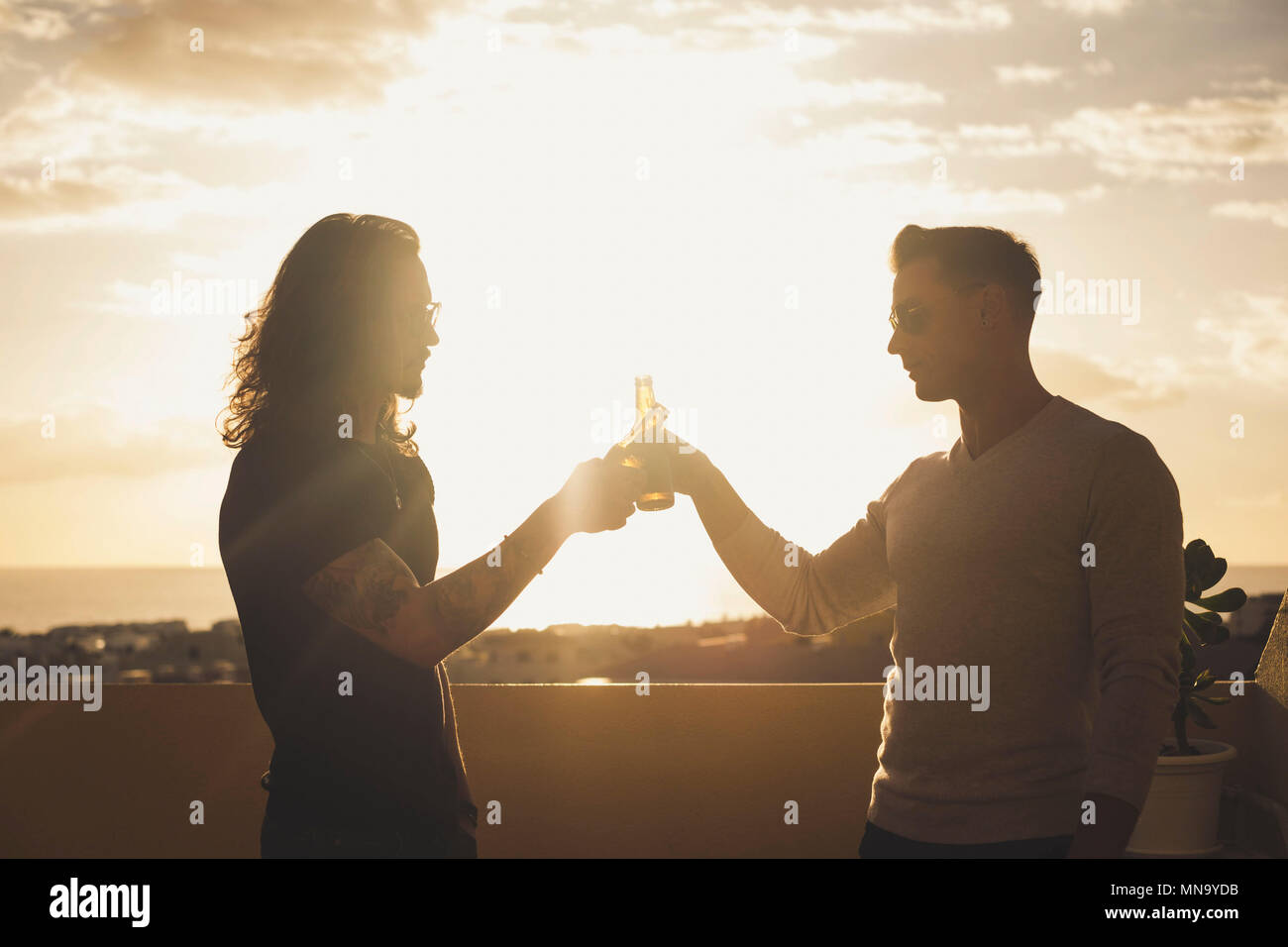 beatiful sunset light and silhouete for two man drinking together on the rooftop terrace with ocean view and buildings. drinking beer to celebrate a s - Stock Image
