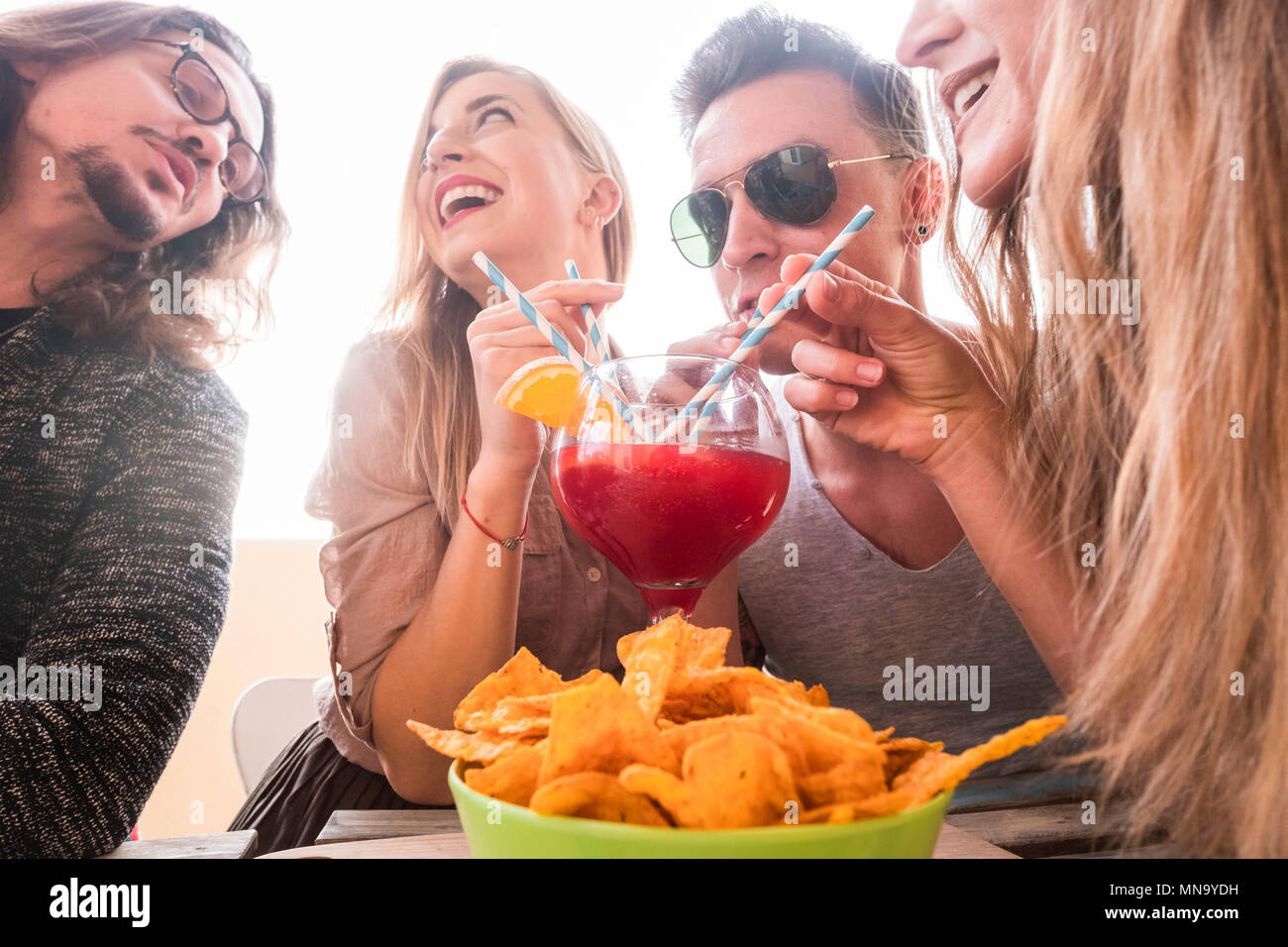 four men and women have fun together friendship drinking all with the same glass vase with red orange fruit. party time with clear background for youn - Stock Image