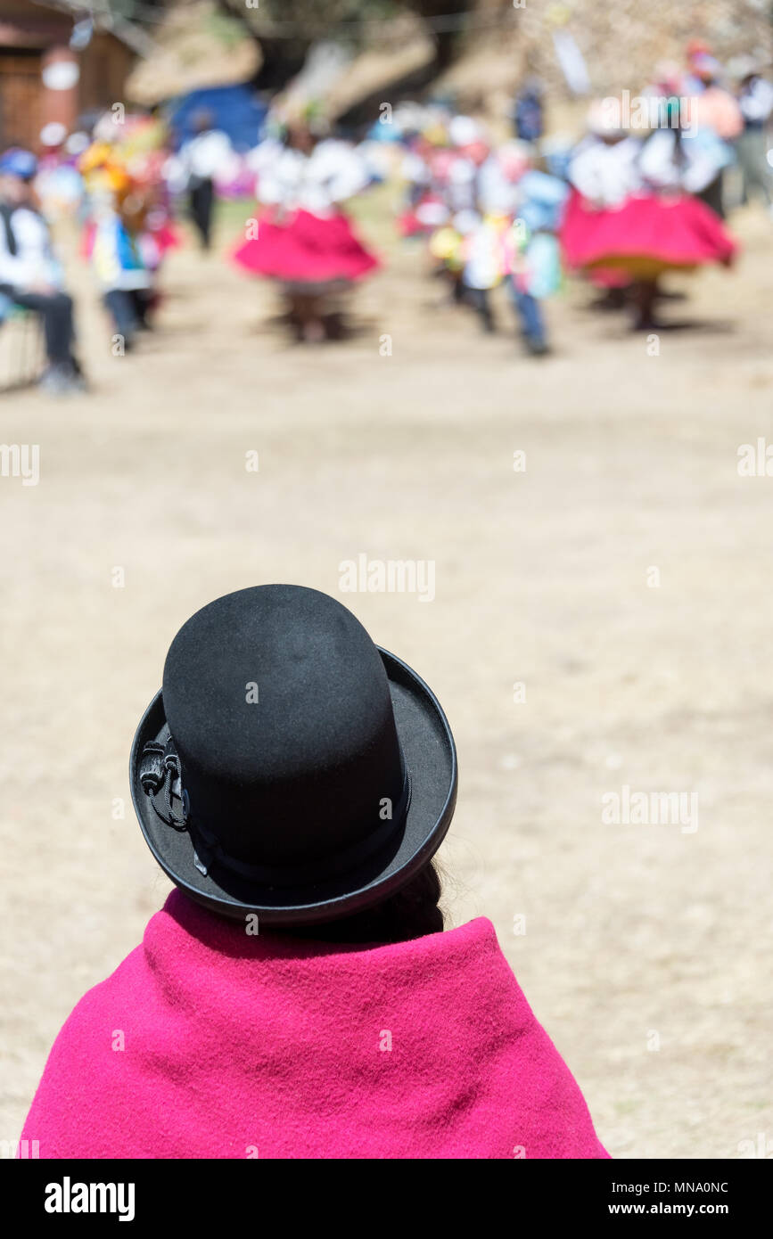 Indigenous woman in traditional dress watching a traditional dance on Isla del Sol in Bolivia - Stock Image