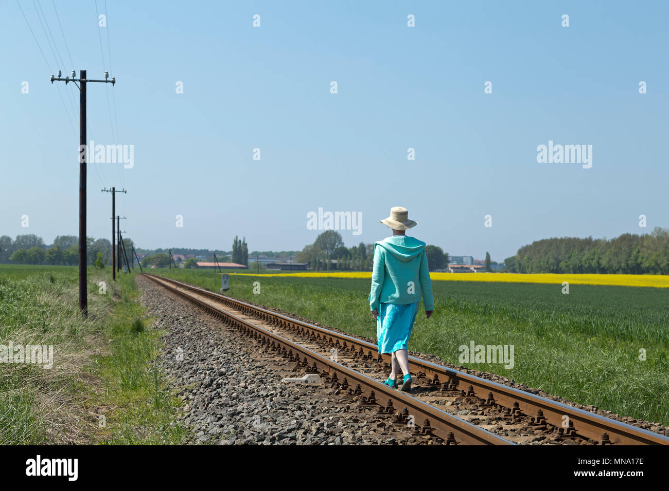 woman walking along railway tracks of the steam train Molli, Klein Bollhagen near Kuehlungsborn, Mecklenburg-West Pomerania, Germany - Stock Image