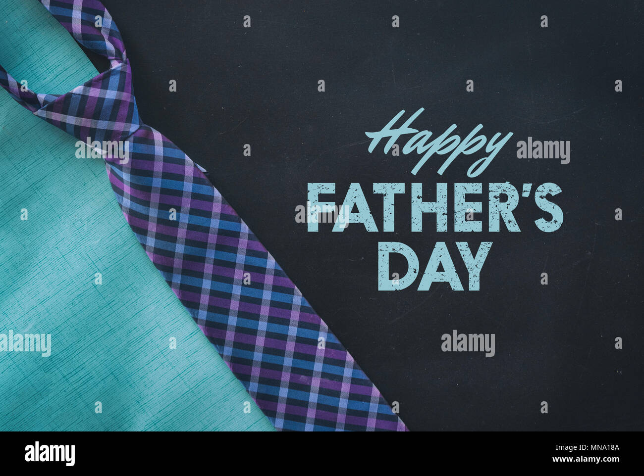 Blue and purple plaid necktie with happy fathers day text for holiday graphic - Stock Image