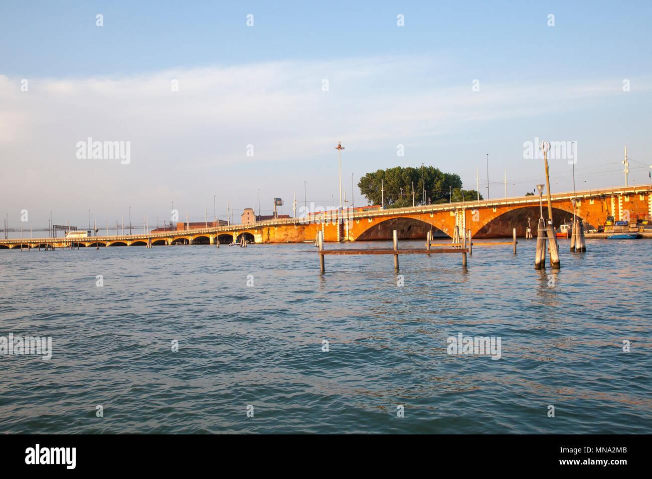 City Tram and van crossing Ponte della Liberta over the Venetian lagoon connecting Venice historic centre with Mestre, Venice, Veneto, Italy at sunset - Stock Image