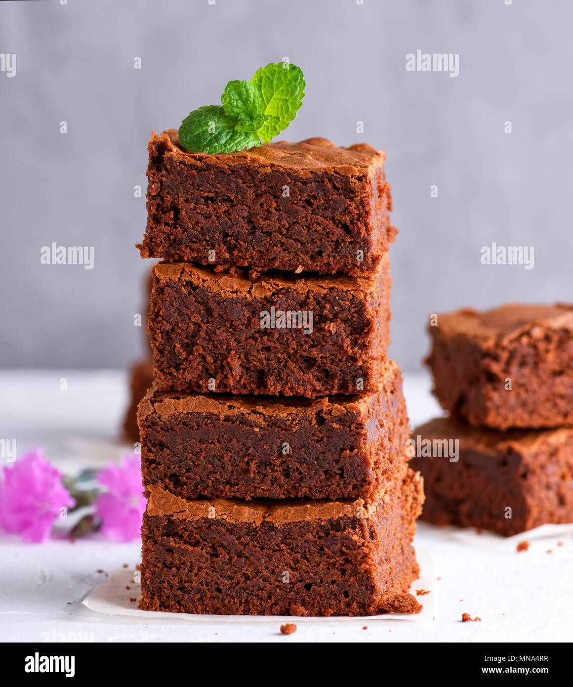 pile of square slices of baked brownie pie on a white surface, close up - Stock Image