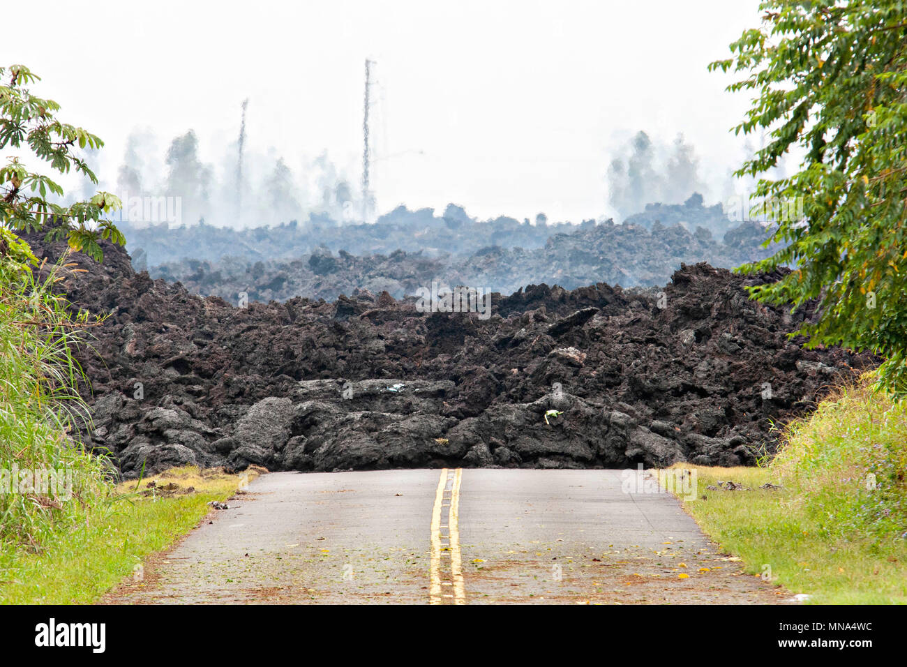 A lava roadblock covers a residential road caused by the Kilauea volcano eruption at Leilani Estates May 12, 2018 in Pahoa, Hawaii. The recent eruption continues destroying homes, forcing evacuations and spewing lava and poison gas on the Big Island of Hawaii. Stock Photo