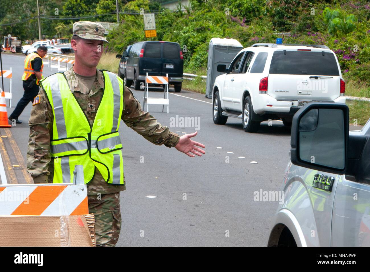 Air Force Spc Donavan Wills, a combat engineer with the 227th Brigade Engineer Battalion, directs traffic in response to the Kilauea volcano eruption at Leilani Estates May 12, 2018 in Pahoa, Hawaii. The recent eruption continues destroying homes, forcing evacuations and spewing lava and poison gas on the Big Island of Hawaii.Stock Photo