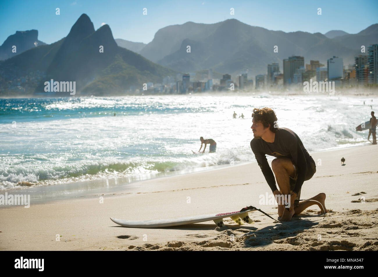 RIO DE JANEIRO - MARCH 20, 2017: Surfer on the beach before heading into the waves at the surf break at Arpoador. - Stock Image