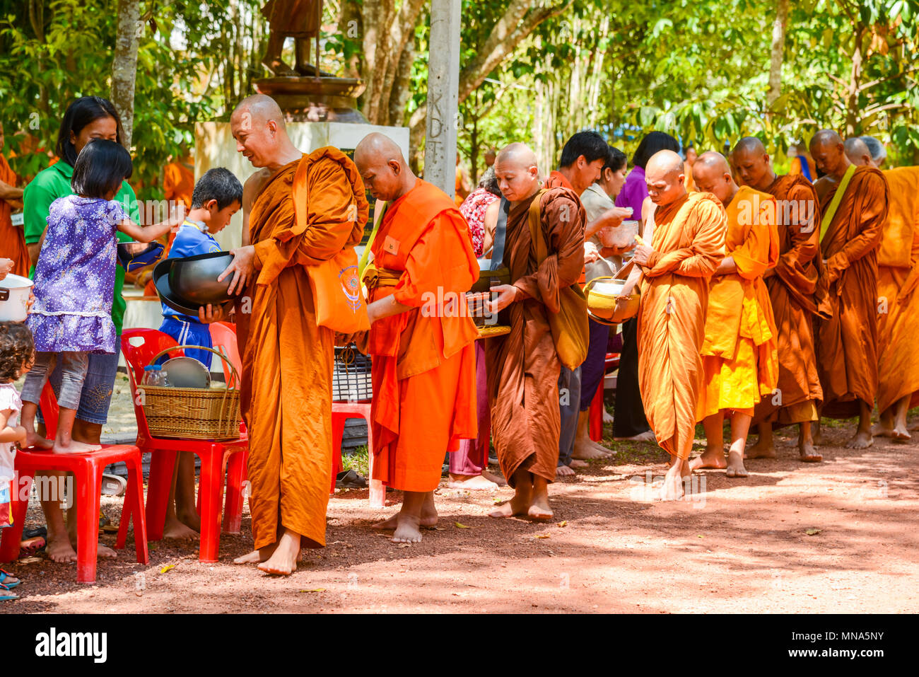 Krabi, Thailand - May 3, 2015: People offering food and things to group of Buddhist monks in morning in public park in Krabi, Thailand - Stock Image