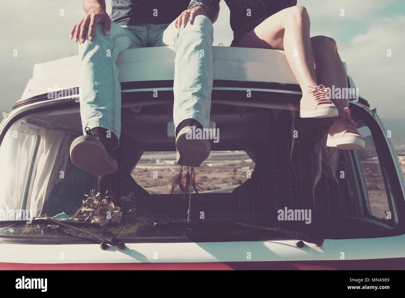 enjoy the vanlife. two pair of young legs sitted on the top of a vintage retro van enjoying the day. travel and discover new places like a desert in b - Stock Image
