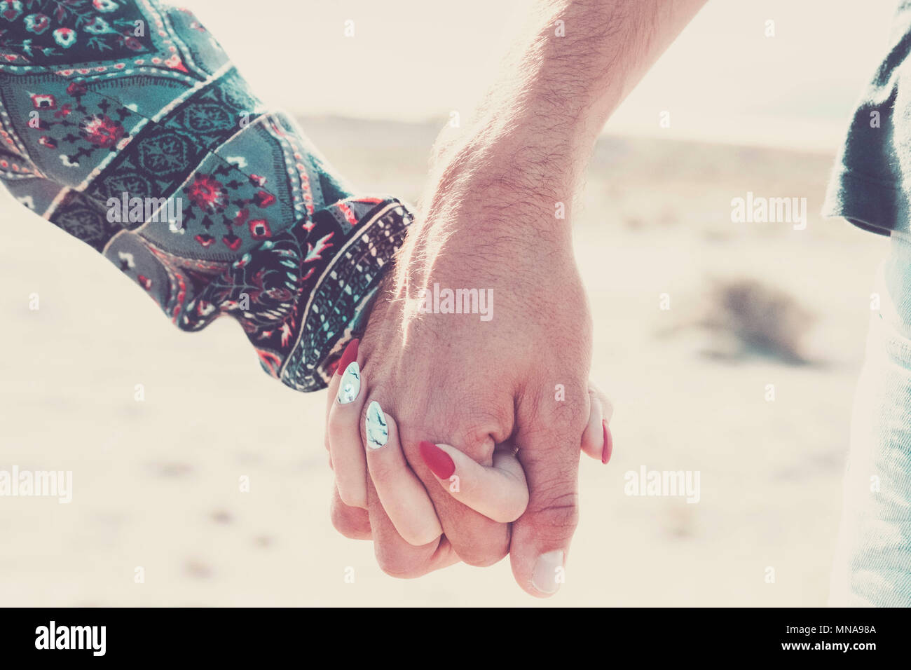 love forever together concept with a pair of caucasian young hands hug and touch under the sunlight. vacation summer time and vintage colors. new mode - Stock Image