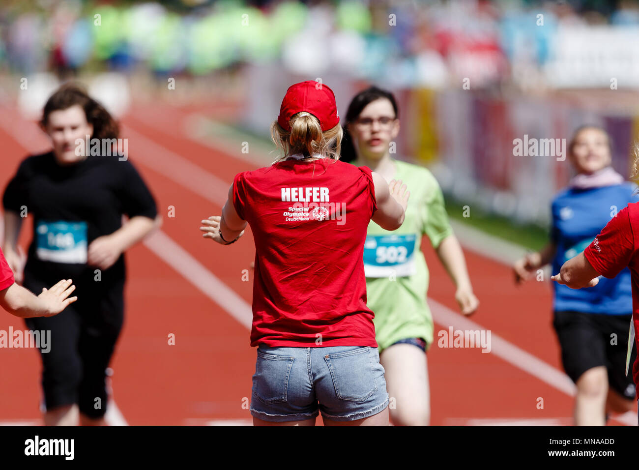 15 May 2018, Germany, Kiel: An assistant receiving runners at the finish line during the Special Olympics, the national summer games for people with psychological or multiple disabilities. The Special Olympics take place between 14 and 18 May 2018. Photo: Frank Molter/dpa - Stock Image
