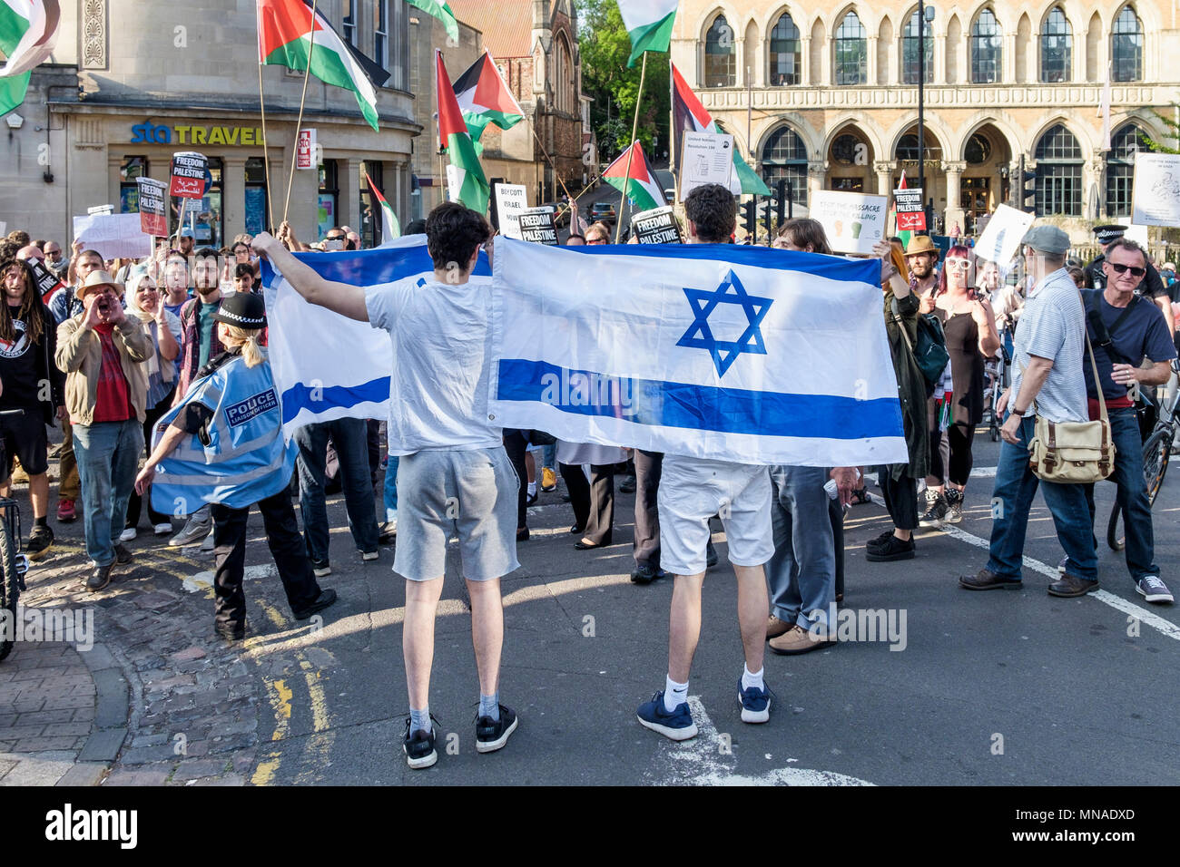 Bristol, UK. 15th May, 2018. A small group of  Pro-Israel supporters carrying the Israeli flag are pictured as they confront Pro-Palestinian demonstrators who were taking part in a protest march through Bristol to show their solidarity with the Palestinian people. The protest march and rally was held to allow people to show their support and solidarity with the Palestinian people after 70 Years of Nakba and to protest about Israel's recent actions in Gaza Credit: lynchpics/Alamy Live News - Stock Image