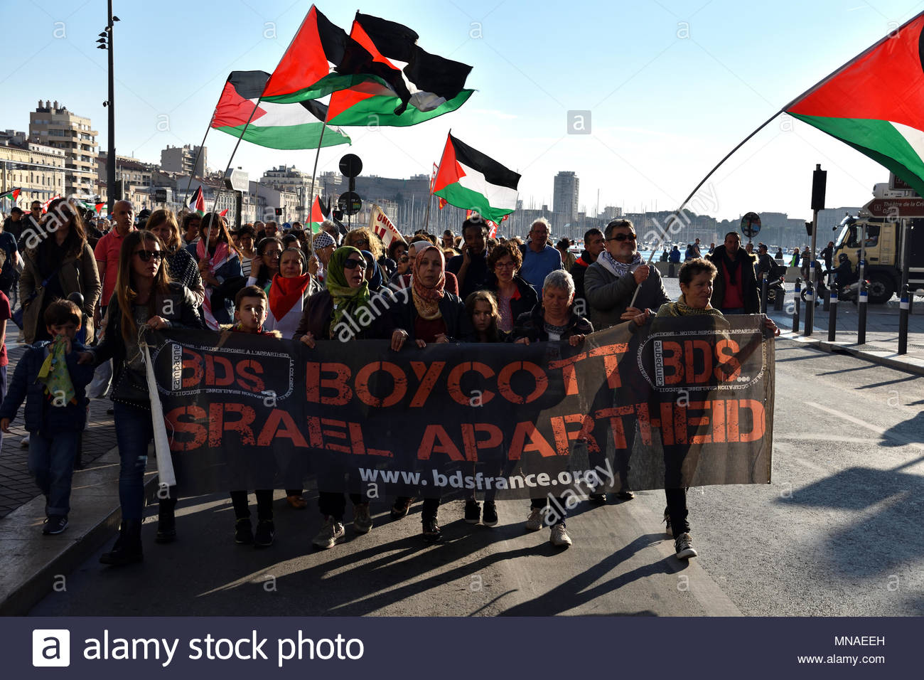Marseille France 15 May 2018 Protesters hold a banner reading 'Boycott Israel Apartheid' and wave Palestinian flags as they take to the streets of Marseille, France on May 15, 2018 during a protest against the killing, the day before, of 59 Palestinians in clashes and protests, on the same day as the United States formally moved its embassy in Israel to Jerusalem from Tel Aviv in defiance of international outrage. (c) copyright CrowdSpark/Gerard Bottino - Stock Image